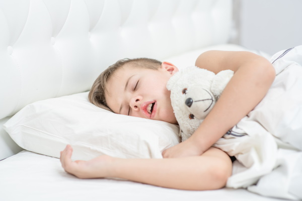 Young boy with toy bear is sleeping with his mouth open, snoring.